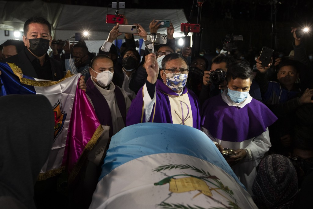 A priest blesses with holy water the remains of Guatemalan migrants who were killed near the U.S.-Mexico border in January, at a memorial Mass in a so...