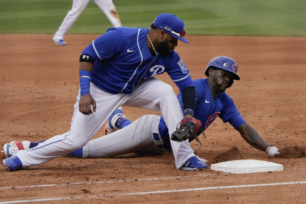 Kansas City Royals first baseman Carlos Santana, left, tags out Chicago Cubs' Cameron Maybin on a pickoff in the fourth inning of a spring training ba...