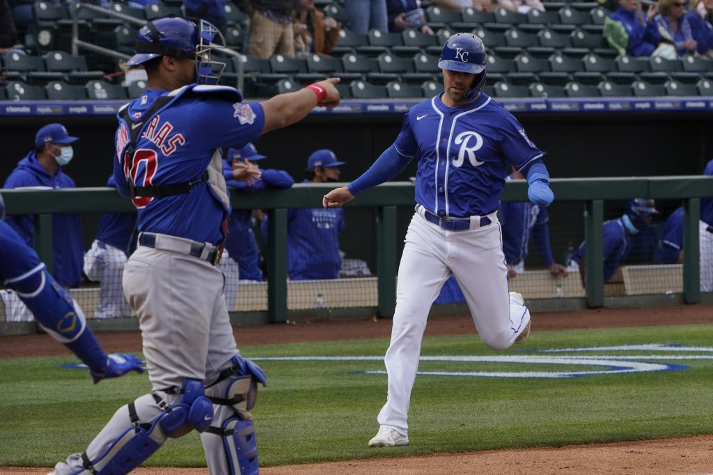 Kansas City Royals' Whit Merrifield runs home on a double by Andrew Benintendi as Chicago Cubs catcher Willson Contreras signals a throw to third base...