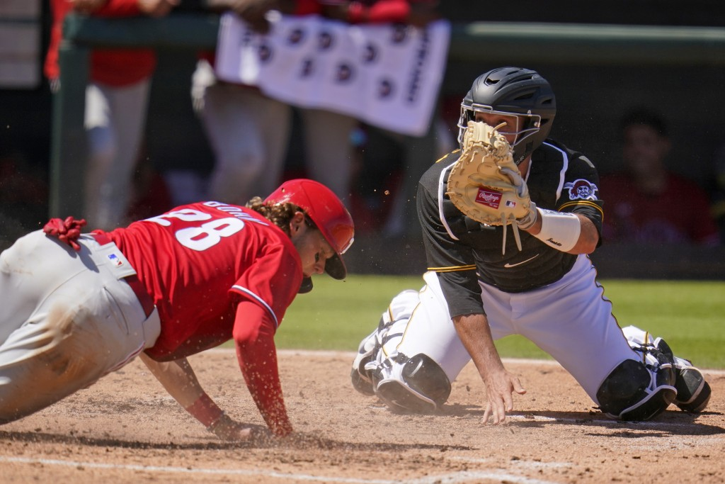 Philadelphia Phillies' Alec Bohm (28) slides safely past a tag-attempt by Pittsburgh Pirates catcher Jacob Stallings to score during the fifth inning ...