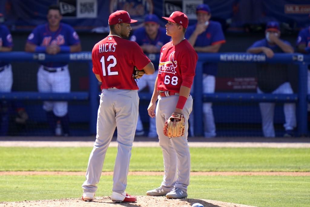St. Louis Cardinals relief pitcher Jordan Hicks (12) talks with third baseman Nolan Gorman (68) after walking New York Mets' Luis Guillorme during the...