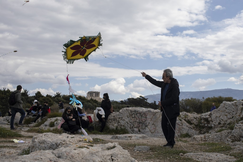 A man flies a kite as in the background stands the ancient Parthenon temple in Athens, on Clean Monday, March 15, 2021. The coronavirus pandemic, whic...