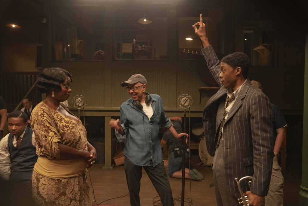This image released by Netflix shows Viola Davis as Ma Rainey, left, director George C. Wolfe, center, and Chadwick Boseman as Levee during the filmin...