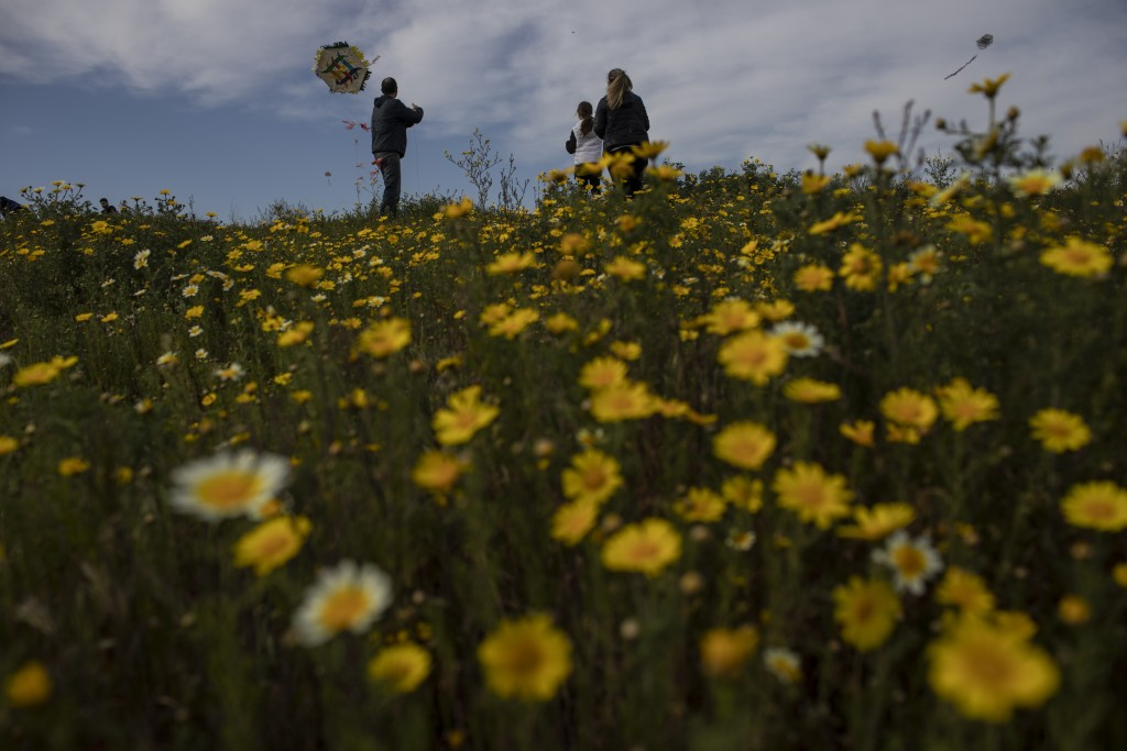 A family tries to fly a kite in a field of flowers in Drapetsona, a suburb of Piraeus, near Athens, on Sunday, March 14, 2021. The coronavirus pandemi...