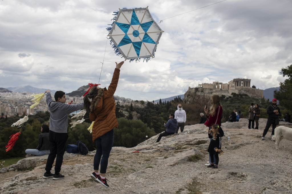 A woman tries to fly a kite as in the background stands the ancient Parthenon temple in Athens, on Clean Monday, March 15, 2021. The coronavirus pande...