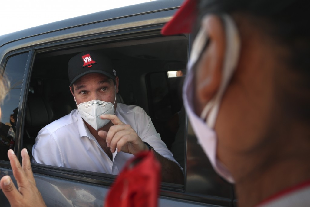 Presidential candidate George Forsyth, with the National Victory party, talks with a supporter as he campaigns in Manchay on the outskirts of Lima, Pe...