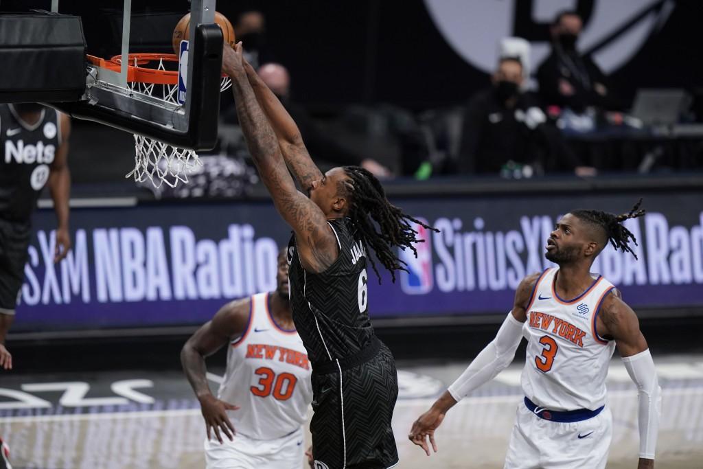 New York Knicks' Nerlens Noel (3) and Julius Randle (30) watch as Brooklyn Nets' DeAndre Jordan (6) dunks the ball during the first half of an NBA bas...