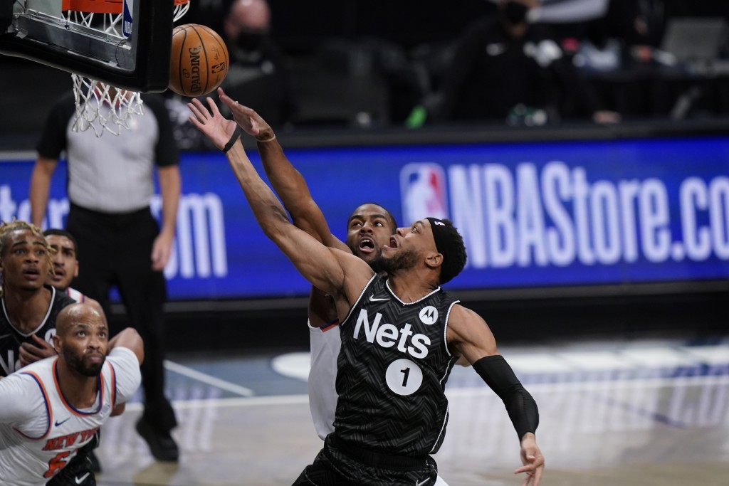 Brooklyn Nets' Bruce Brown (1) drives past New York Knicks' Alec Burks during the first half of an NBA basketball game Monday, March 15, 2021, in New ...