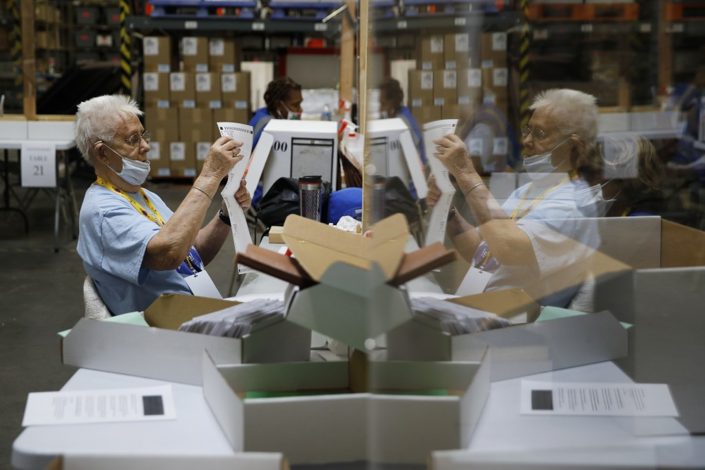 FILE - In this June 9, 2020, file photo, election workers process mail-in ballots during a nearly all-mail primary election in Las Vegas. A surge of a...