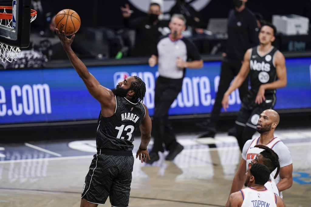Brooklyn Nets' James Harden, left, drives past New York Knicks' Taj Gibson, right, and Obi Toppin during the first half of an NBA basketball game Mond...