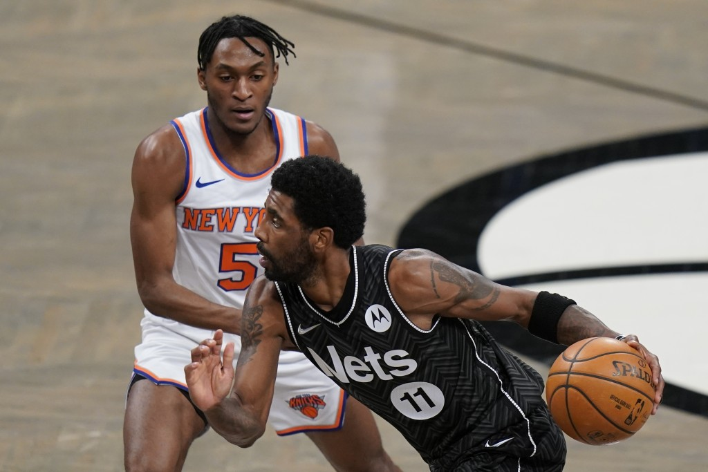 Brooklyn Nets' Kyrie Irving (11) drives past New York Knicks' Immanuel Quickley (5) during the first half of an NBA basketball game Monday, March 15, ...