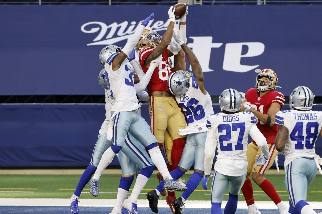 FILE - San Francisco 49ers wide receiver Kendrick Bourne (84) leaps above Dallas Cowboys' Donovan Wilson, left, and Jourdan Lewis (26) to catch a Hail...