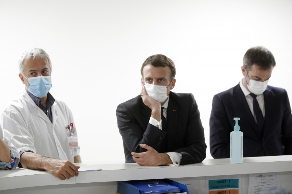 French President Emmanuel Macron, French Health Minister Olivier Veran, right, and Chief of Intensive Care Unit Dr. Jan Hayon listen to staff working ...