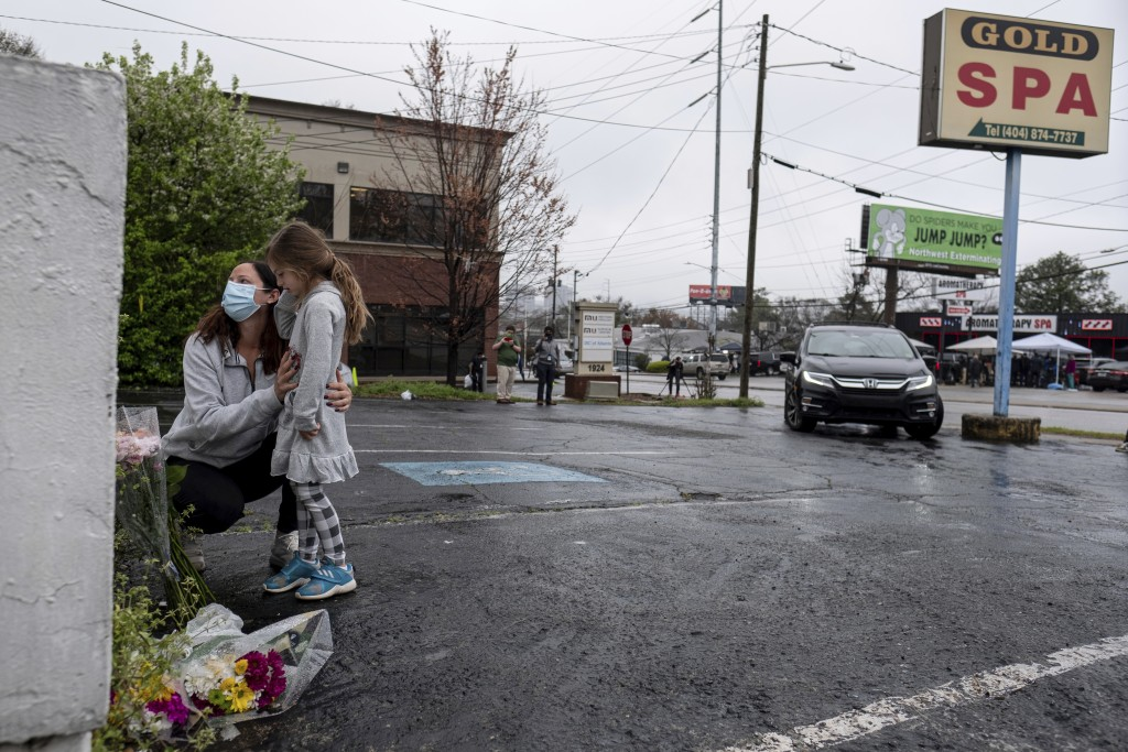 Mallory Rahman and her daughter Zara Rahman, 4, who live nearby, pause after bringing flowers to the Gold Spa massage parlor in Atlanta, Wednesday aft...