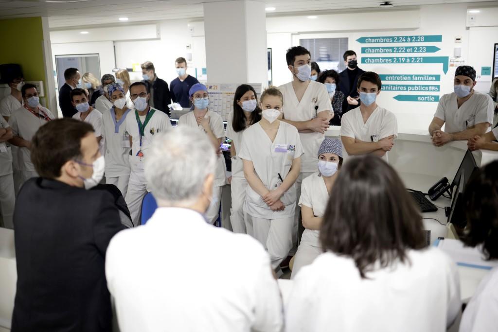 French President Emmanuel Macron, left, speaks with staff working in the intensive care ward of the Poissy/Saint-Germain-en-Laye hospital, near Paris,...