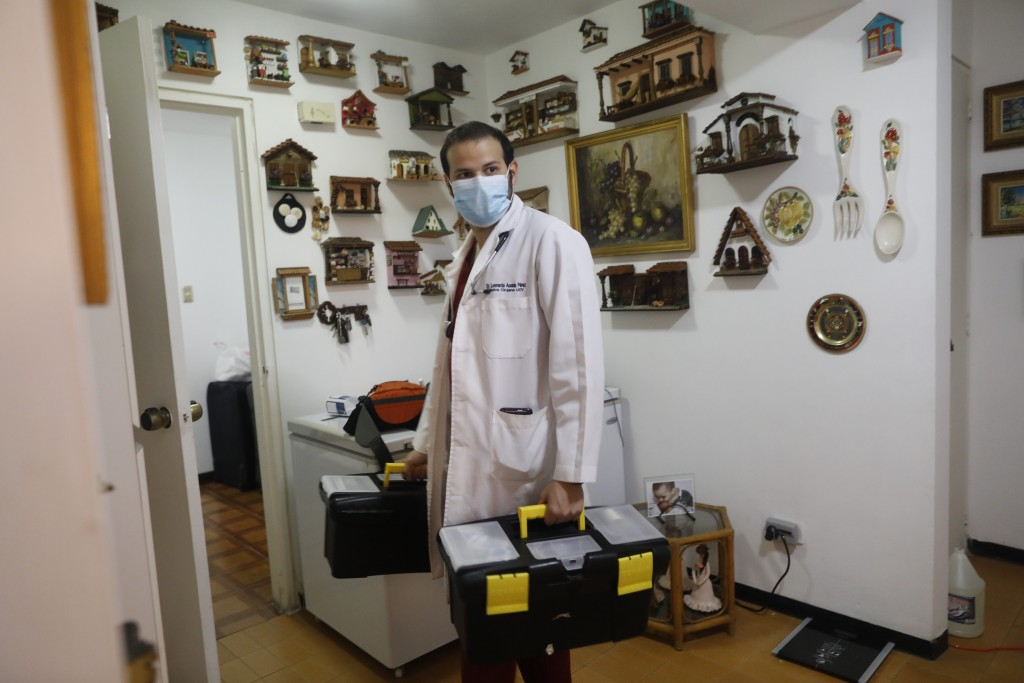 Doctor Leonardo Acosta holds two cases with medical supplies as he leaves the apartment of two patients he just checked on, who suffer from COVID-19 i...