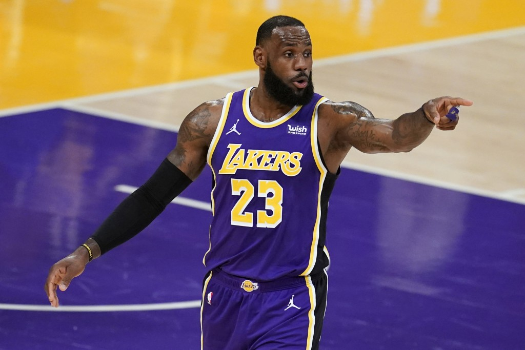 Los Angeles Lakers forward LeBron James signals to a teammate during the first half of an NBA basketball game against the Charlotte Hornets on Thursda...
