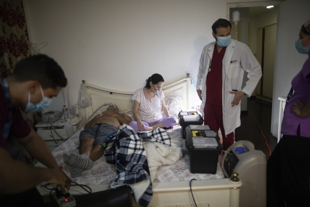 Carmen Lares who suffers from COVID-19, along with her husband Oscar Lares, on the left side of the bed, and who is connected to a non-invasive mechan...