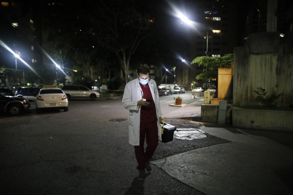Doctor Leonardo Acosta checks his cell phone as he arrives for a medical care visit of a patient who suffers from COVID-19 at a building in Caracas, V...