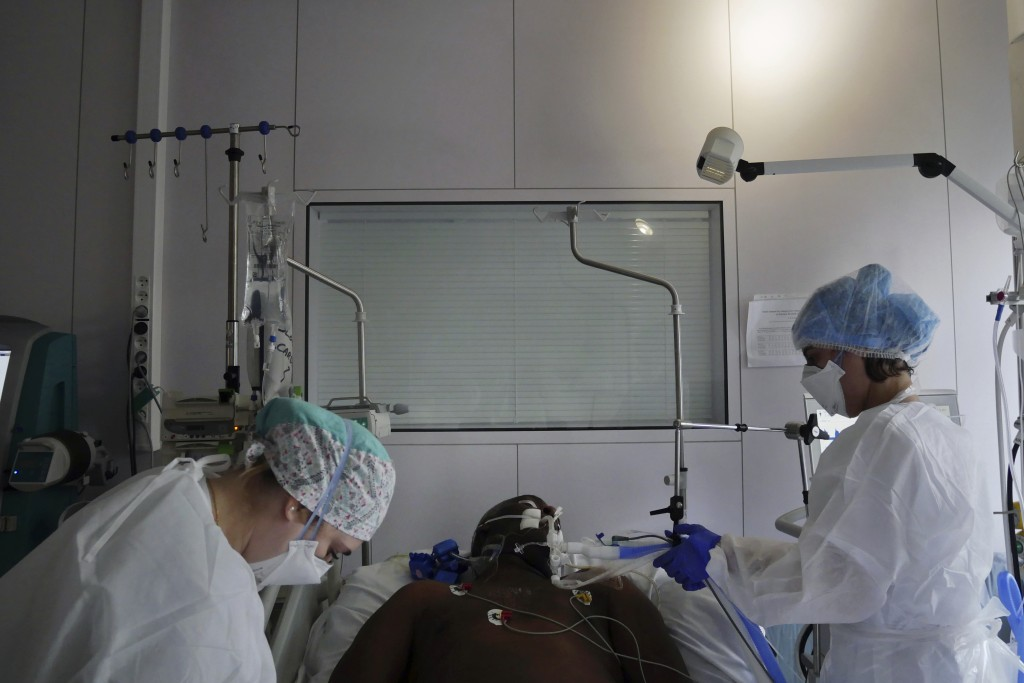 Nurses Stephanie Dias, right, and Segolene Poux tend to a patient affected by COVID-19 virus in the ICU unit at the Ambroise Pare clinic in Neuilly-su...