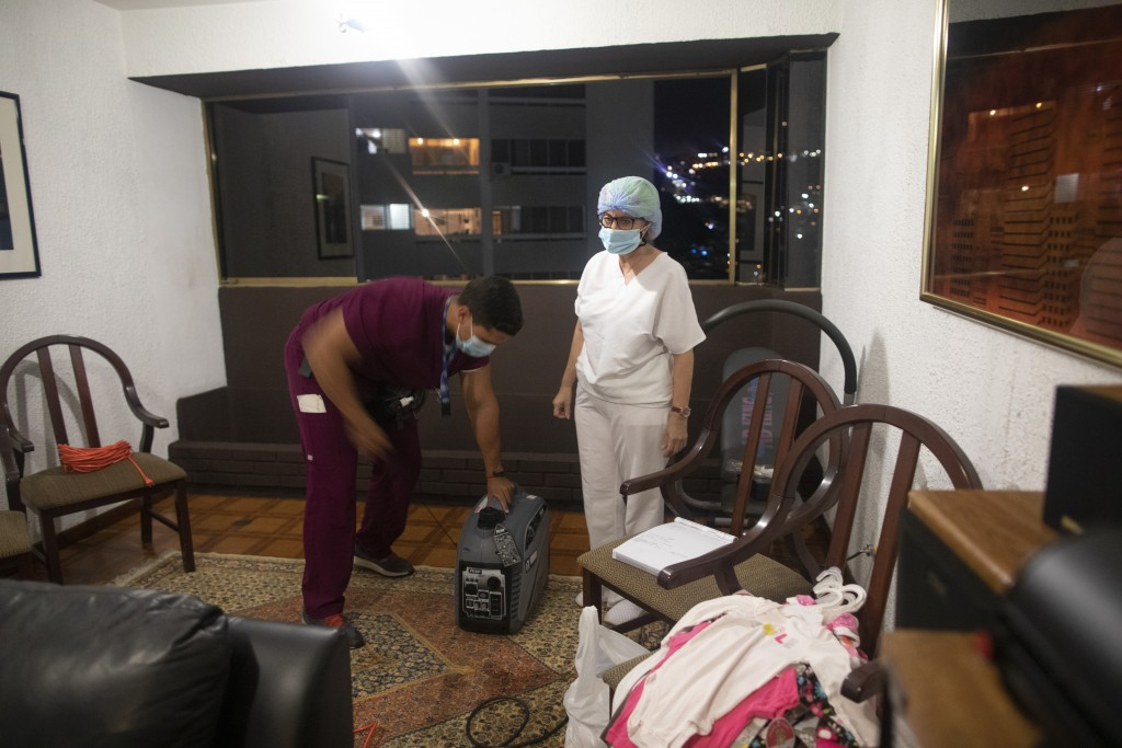 Alberto Alfonso turns on a generator to keep oxygen concentrators working as nurse Marlene Cabezasstand stands next to him in the living room of the L...