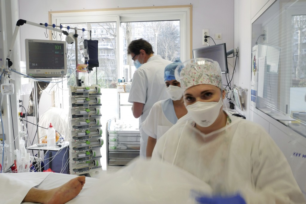 Nurses Stephanie Dias, center, and Segolene Poux, right, tend to a patient affected by COVID-19 virus in the ICU unit at the Ambroise Pare clinic in N...