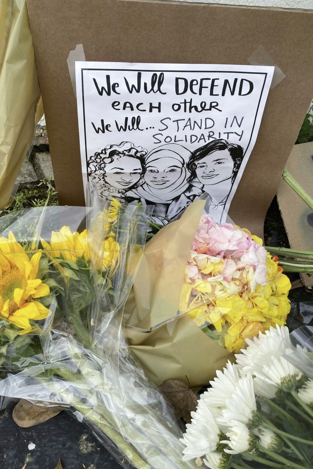 Flowers, candles and signs are displayed at a makeshift memorial on Friday, March 19, 2021, in Atlanta.  Robert Aaron Long, a white man, is accused of...