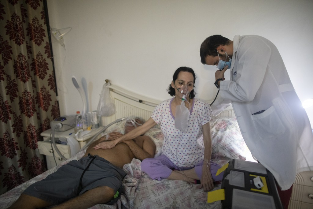 Doctor Leonardo Acosta, right, listens to the lungs of Carmen Lares who suffers from COVID-19 along with her husband Oscar Lares, on the left side of ...