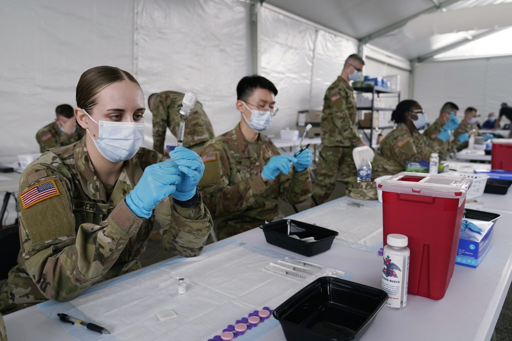 FILE - In this March 9, 2021, file photo, Army health specialists fill syringes with the Pfizer COVID-19 vaccine in Miami. Despite the clamor to speed...