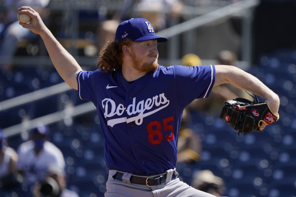Los Angeles Dodgers' Dustin May pitches during the first inning of the team's spring training baseball game against the San Diego Padres, Saturday, Ma...