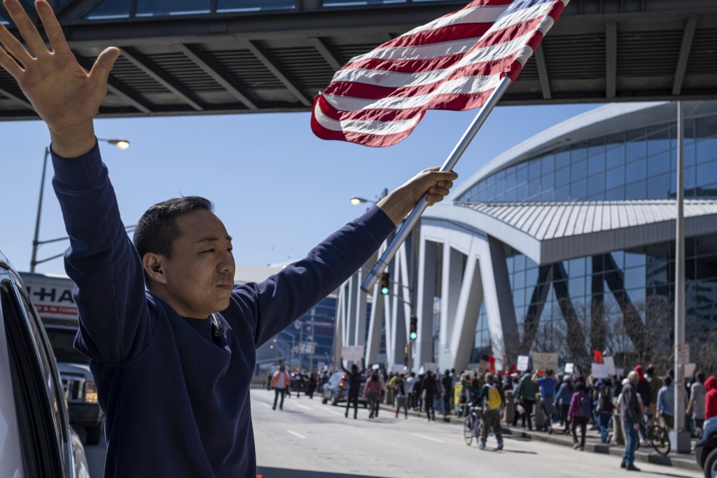 """Hailun Song waves a U.S. flag and cheers marchers as a """"stop Asian hate"""" rally in downtown Atlanta passes by Saturday afternoon, March 20, 2021. (AP P..."""