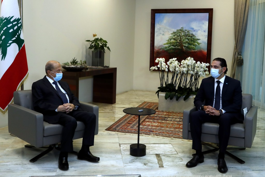 In this photo released by the Lebanese government, Lebanese President Michel Aoun, left, meets with Lebanese Prime Minister-Designate Saad Hariri, at ...