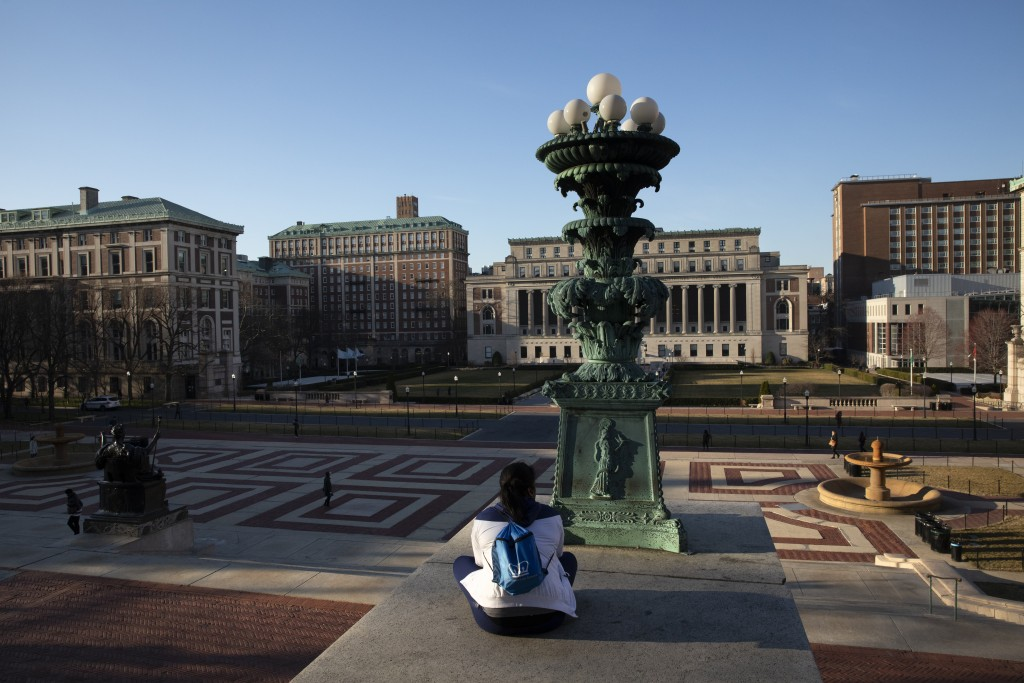 FILE - In this Monday, March 9, 2020 file photo, A woman sits on the Columbia University campus, Monday, March 9, 2020, in New York. Colleges througho...