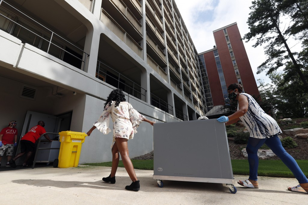 FILE - In this  Friday, July 31, 2020 file photo, College students begin moving in for the fall semester at N.C. State University in Raleigh, N.C. Col...