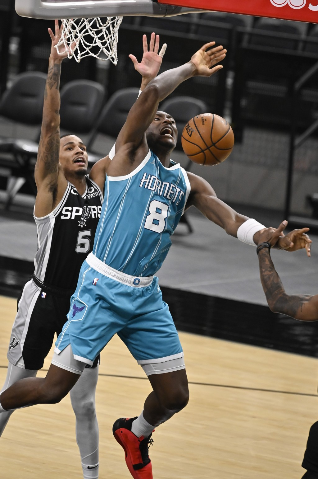 Charlotte Hornets' Bismack Biyombo (8) is fouled by San Antonio Spurs' Dejounte Murray during the second half of an NBA basketball game on Monday, Mar...
