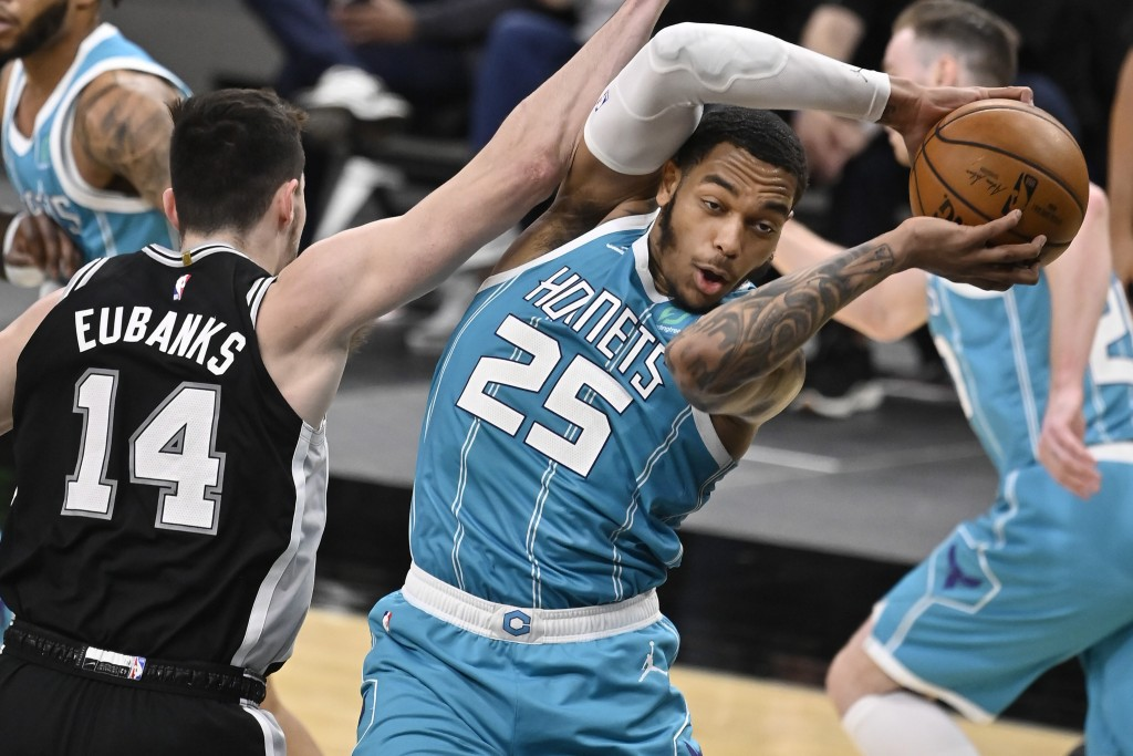 Charlotte Hornets' P.J. Washington (25) grabs a rebound from San Antonio Spurs' Drew Eubanks during the first half of an NBA basketball game on Monday...