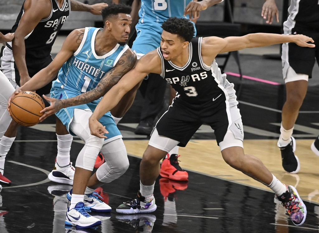 San Antonio Spurs' Keldon Johnson (3) attempts to steal the ball from Charlotte Hornets' Malik Monk during the first half of an NBA basketball game on...