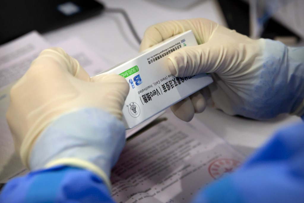 A worker opens a package of coronavirus vaccine made by a Sinopharm subsidiary during a COVID-19 vaccination session for resident foreign journalists ...