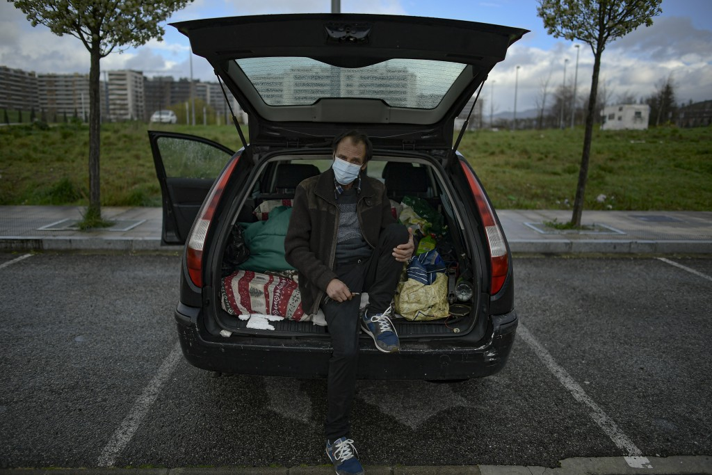 Juan Jimenez, 60, poses by his car which is now his home in Pamplona, northern Spain, Friday, March 19, 2021. Jimenez has been forced to dwell in his ...