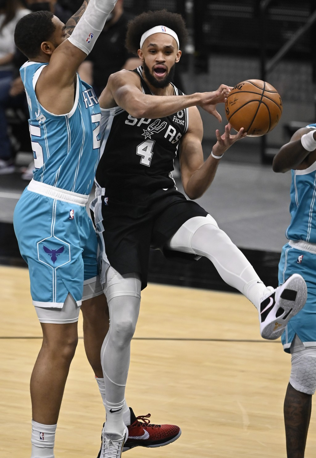 San Antonio Spurs' Derrick White (4) looks to pass as he is defended by Charlotte Hornets' P.J. Washington during the first half of an NBA basketball ...