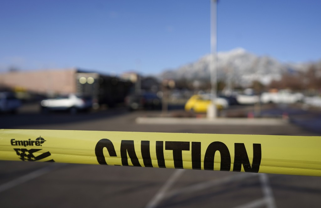 Caution tape marks the parking lot outside a King Soopers grocery store where a mass shooting took place a day earlier in Boulder, Colo., Tuesday, Mar...