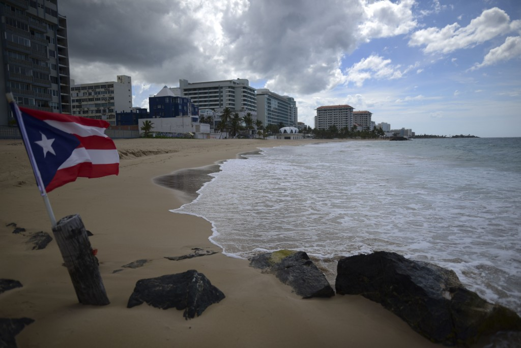 FILE - In this May 21, 2020 file photo, a Puerto Rican flag flies on an empty beach at Ocean Park, in San Juan, Puerto Rico. The number of tourists ar...