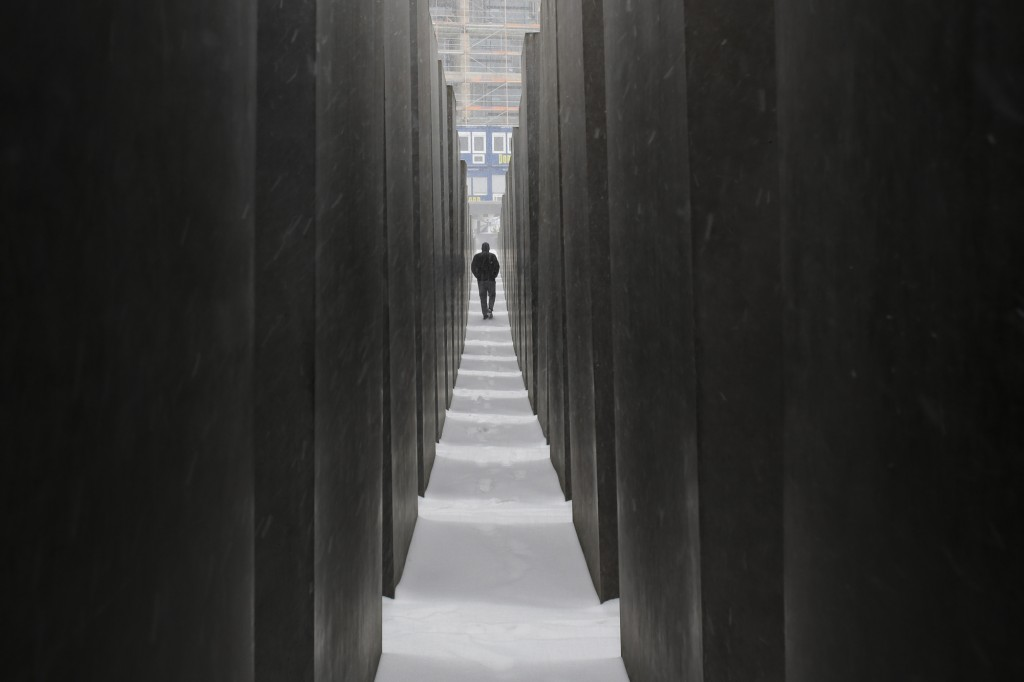 FILE - In this Feb.7, 2021 file photo a man visits the Holocaust Memorial during snowfall in central Berlin, Germany. Germany has committed millions o...