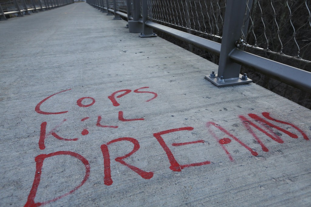 Writing is seen on the Columbia Street Pedestrian Bridge over Six Mile Creek, Monday, March 22, 2021, in Ithaca, N.Y.  The nationwide reexamination of...