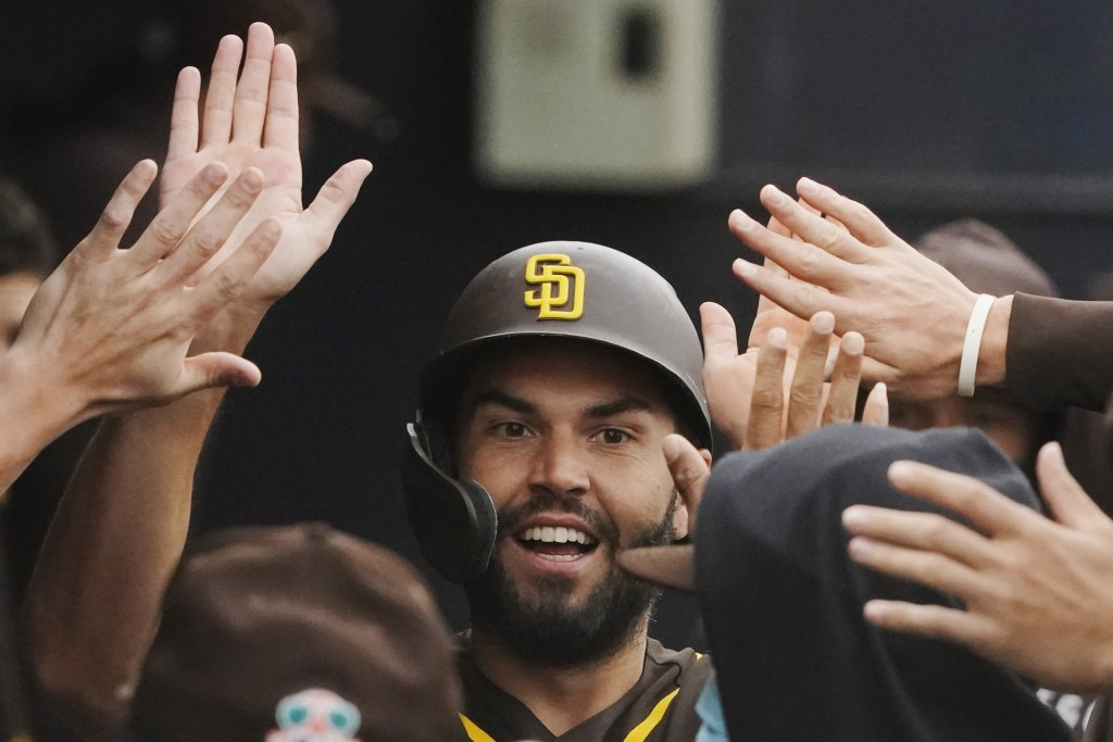 San Diego Padres' Eric Hosmer celebrates with teammates in the dugout after scoring a single hit by Wil Myers in the first inning of spring training b...