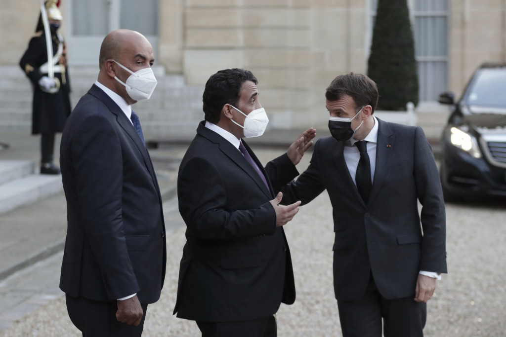 French President Emmanuel Macron, right, talks with Mohammad Younes Menfi, president of Libya's Presidential Council, center, and Musa al-Koni, vice-p...