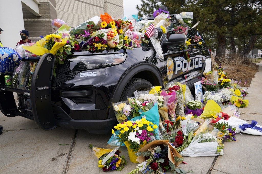 Police cruiser parked outside Boulder Police Department is covered with bouquets in tribute after an officer was one of the victims of a mass shooting...