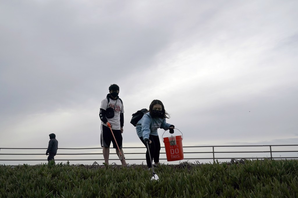 Pacifica Beach Coalition volunteers Alec Juntura, 21, foreground left, and Kimmy Tran, 20, pick up trash near Sharp Park Beach in Pacifica, Calif., We...