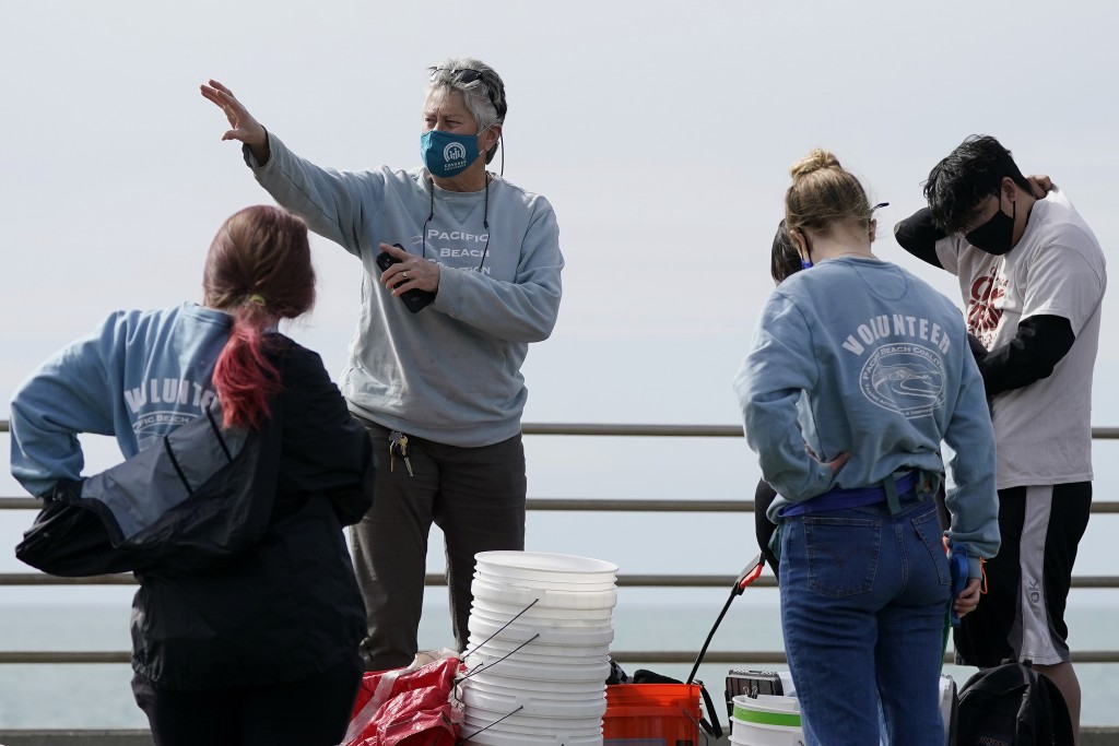 Lynn Adams, president of the Pacifica Beach Coalition, center, gives directions to volunteers before they clean areas near Sharp Park Beach in Pacific...