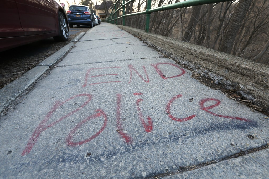 Writing is seen on the sidewalk on Giles Street, Monday, March 22, 2021, in Ithaca, N.Y.   The nationwide reexamination of policing after the killing ...